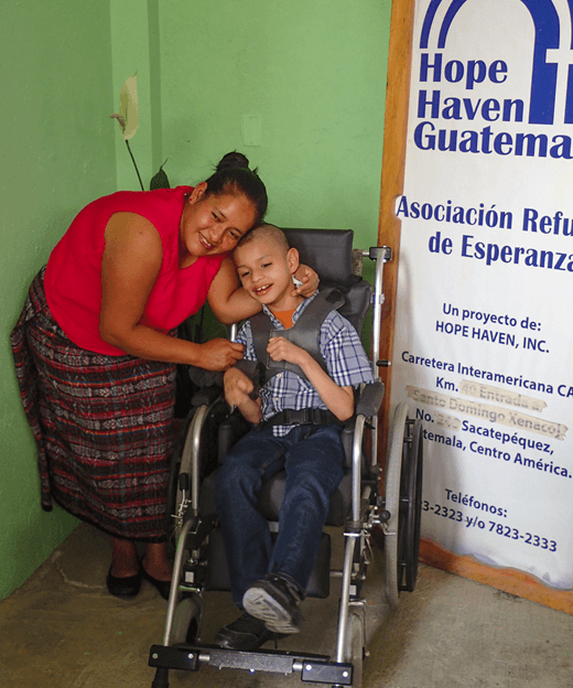Smiling child in wheelchair with mother